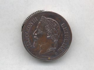 "Circular, in the shape of a five Franc coin, with raised decoration of the Emperor in profile with laurel wreath on his head, inscribed on perimeter ""Napoleon III, Empereur,"" ""Barre"" inscribed below, reverse features coat-of-arms, inscribed ""Empire Francais, 5F, 1870."" Wedge shaped piece swings out of container at top to reveal interior match compartment. Striker attached to side."