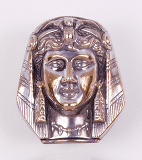 In the shape of a woman's head, dressed in exotic, Egyptian style headdress; she wears long pendant earrings in the shape of obelisks with heiroglyphics, and necklace strung with smaller pendants. Front and reverse decoration identical. Box lid with thumb catch on bottom, hinged on reverse. Striker on bottom of lid.