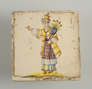 Standing man, pointing to the left and carrying winged and flowered blue staff in his left hand; dress of layers of bluish-white and manganese skirts, with yellow coat; high head dress. Chinoiserie type of decoration.