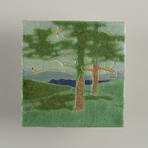 A glazed tile with a landscape scene including two trees.