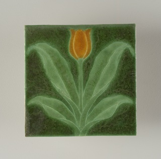 "Coarse white earthenware body with press-molded design of single tulip and leaves.  Mat glazes in dark red and light green, with butterscotch mat glaze on blossom.  The tulip lossom is divided symetrically by thin walls of clay, the raised contours partitioning the inlaid glazes.  Palette is naturalistic with ""Grueby green"" between the leaves and the background."