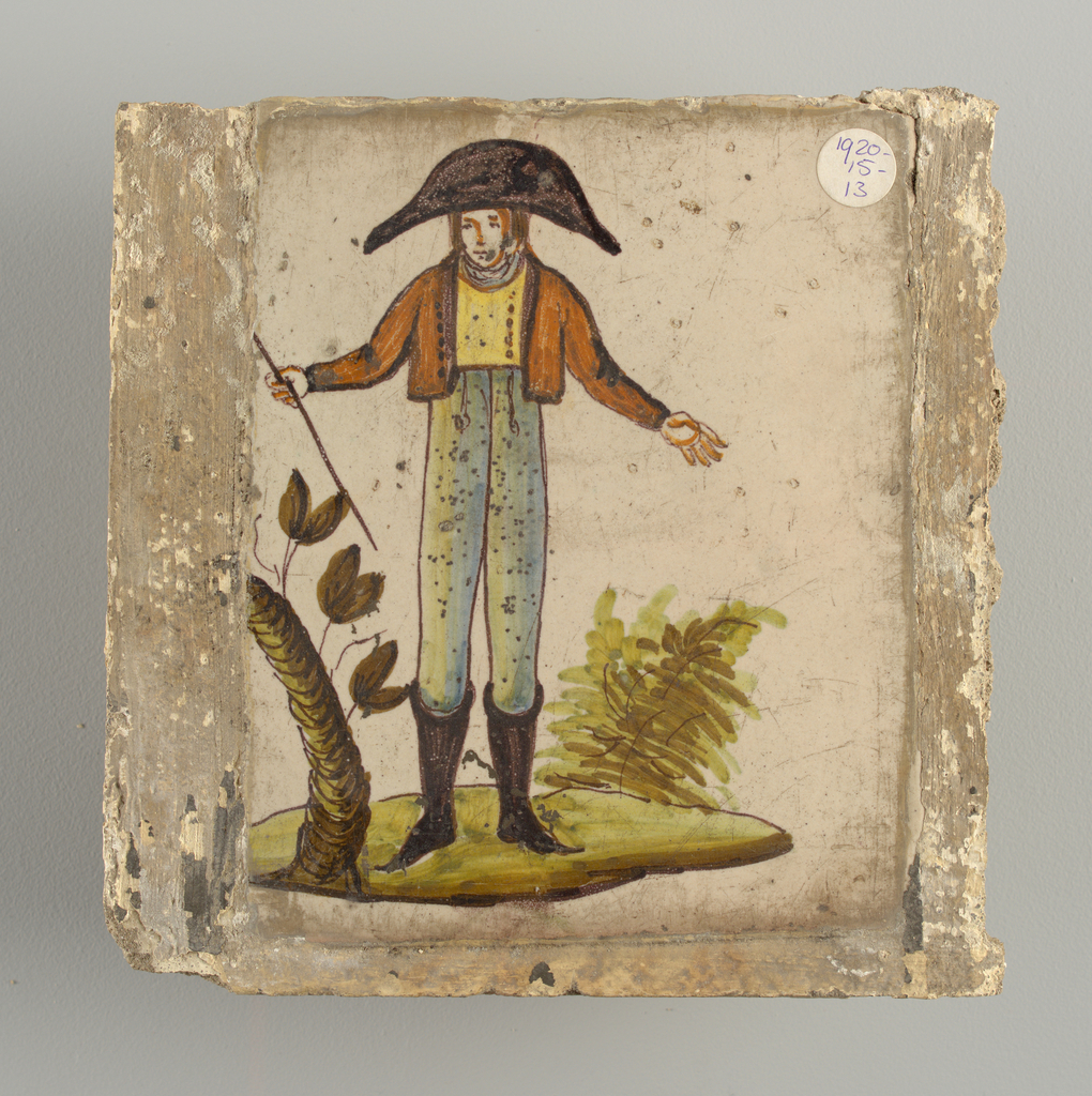 Man in high boots, white breeches and brown jacket, wearing bicorn hat, and holding a stick in his right hand. Tree trunk with a few leaves at the left.