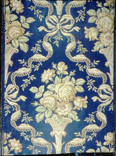 Embossed floral bouquet, surrounded by ribbon diaper pattern with bowknot at top and sides, printed in reds and tans on deep blue ground.