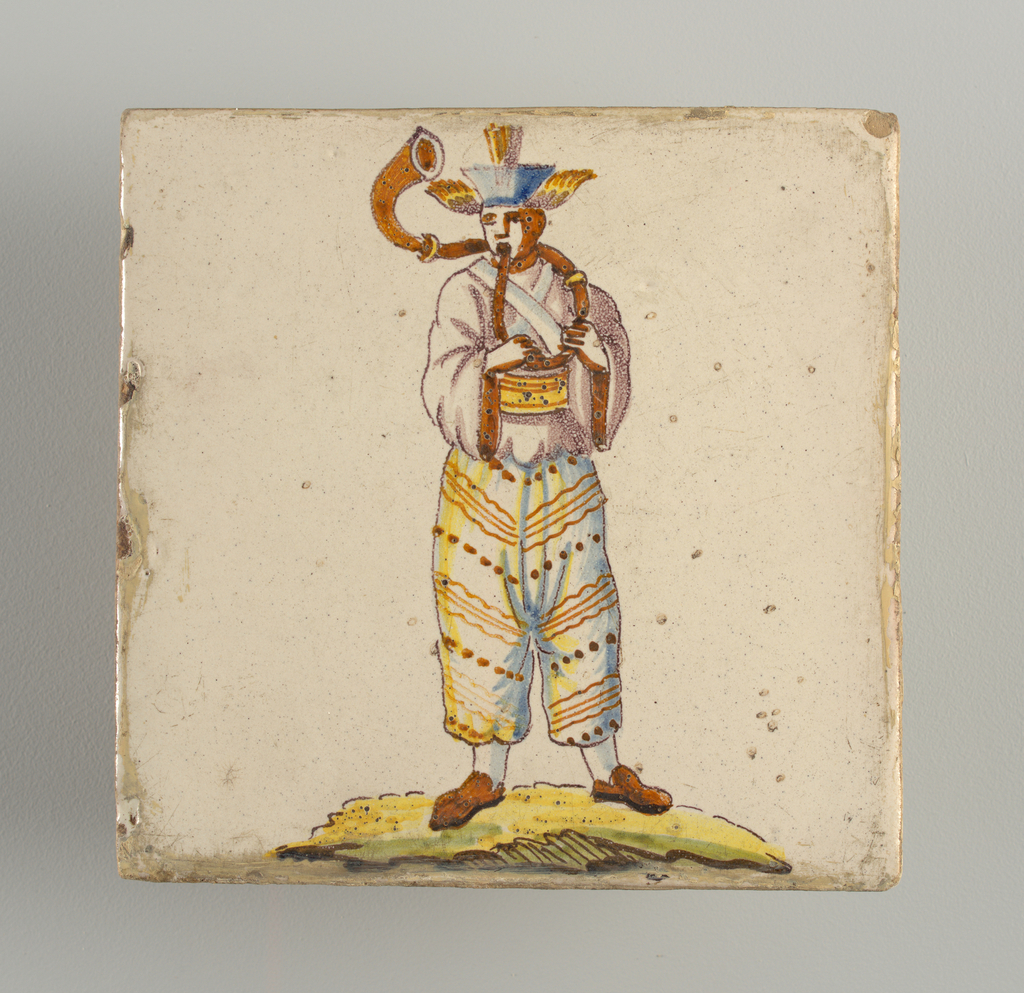 Standing man, dressed in fancy Oriental costume and winged head-dress, playing a horn. Chinoiserie type of decoration.