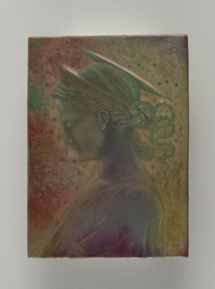 Molded red earthenware body modeled in low relief with a Pre-Raphaelitesque left profile of a woman wearing a coronet and having slightly trailing hair. Halo-like image above her head. Decoration of metallic lustres on an iridescent ground, predominately in shades of purple and green.