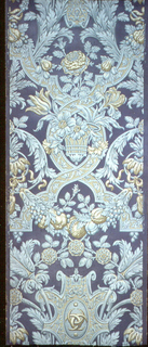 """Embossed armorial pattern with garland of fruit, basket of flowers, three-crescent symbol, and stippled strapwork. Printed on selvedge: """"Patented in U.S.A."""" Printed in shades of olive green and three shades of aqua on dark blue ground."""