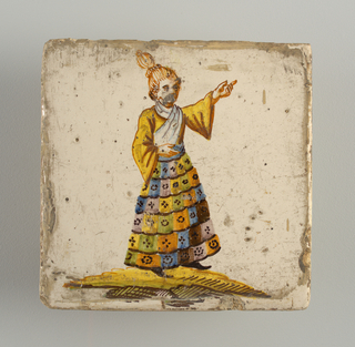 Standing man, left arm raised and pointing to upper corner; dressed in multi-colored checkered skirt, yellow shirt and white shawl. Chinoiserie type of decoration.