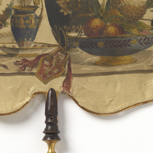 Handscreen with a wide, octogonal silk leaf printed with a still life of neoclassical pottery, fruits, birds and feathers in the late 18th century style. Turned and gilded wood handle.