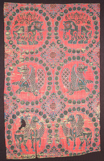 Fragment of woven silk containing six pearl roundels, in sky blue and dark green on a red ground. The top two roundels enclose confronted elephants, the middle two addorsed senmurvs, and the bottom two confronted hippocampi. Four-lobed rosettes with elaborate floriated edges in interspaces.