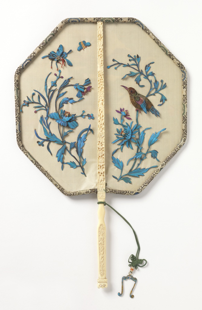 Handscreen with octogonal leaf and carved ivory handle. Cream-colored silk gauze leaf has a design of flowering plants, birds and insects, formed from kingfisher and other feathers. The frame is wrapped with brocaded silk. The handle is ornamented with a knotted green silk cord, glass beads and an embroidered and gilded pendant.