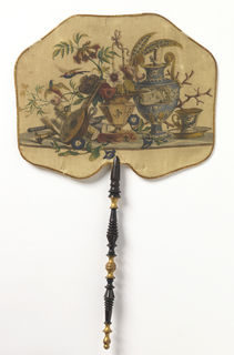 Handscreen with wide octogonal silk leaf leaf printed with a still life of pottery, birds and instruments in the late 18th century style. Turned and gilded wood handle.