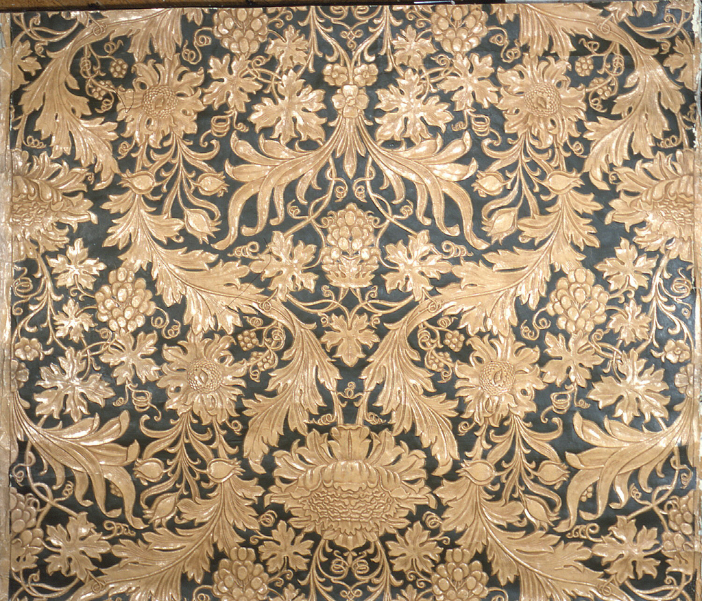 Imitation leather. Embossed symmetricaly arranged floral (sunflowers), fruit (grapes), and foliate (acanthus) design; printed in slate gray, beige. Similar to Morris Sunflower pattern.