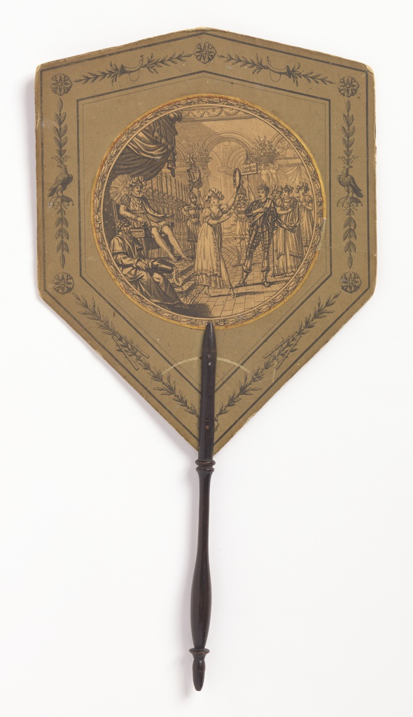 """Shield-shaped handscreen, round center medallion shows a woman dancing and playing the tambourine before the king and court; a soldier holds a standard reading """"Simplicité, Constance"""""""