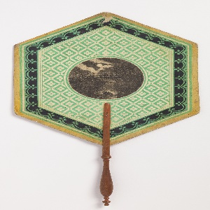 Hexagonal handscreen with a circular medallion in the center with a classical scene, surrounded by floral borders in green and white.