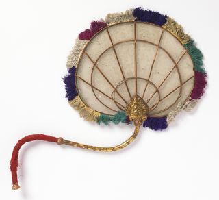 Handscreen with a curving handle of gilded wood, with one end wrapped in red silk. Translucent (mica?)leaf is painted in white with loose hatching and vase pattern. Radiating framework of gold. Edged with multicoloured silk fringe.