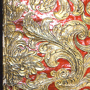 Embossed, symmetrical rococo design of floral amd acanthus foliate pattern. Printed in dark red lacquer and metallic gold.