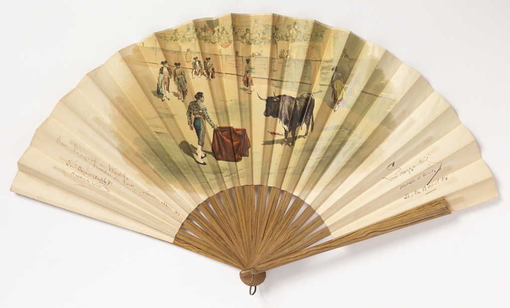 Pleated fan. Obverse has a bullfighting scene in the center with signatures of bullfighters to the right and left. Reverse has a tavern scene. Sticks are plain wood with varnish.
