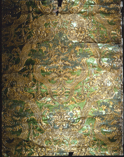Imitation leather. Embossed symmetrical rococo floral and foliate pattern, with some areas in stippled texture; printed in metallic bright green and metallic gold.