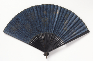 Pleated fan. Paper leaf painted on both sides with spots and silver florals. Wood sticks painted black. Pink silk ribbon.