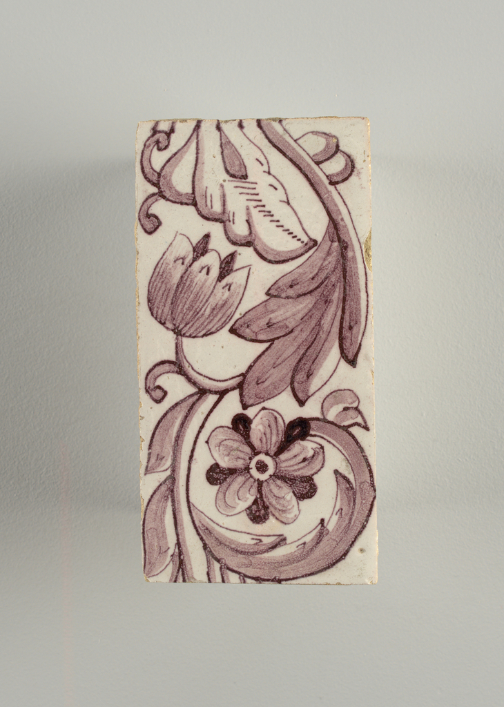 Vertical rectangles. Each tile with identical pattern of two flowers and leaves on continuous scrolling stem. One flower faces the observer and the other is in profile. Manganese violet on white ground.