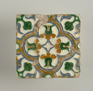 Moulded in low relief, with white, blue, green, and brown glaze. Quatrefoil design, with conventionalized floral and foliate forms.