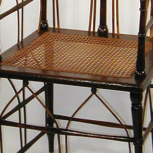 Tall-backed chair in the gothic style, frame consisting of thin rods of wood, some bent to resemble arched gothic windows; square seat with woven wicker.