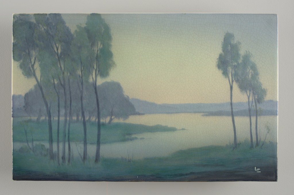 White clay body, cast.  Rectangular plaque set into wooden frame.  Underglaze decorated with scene of a lake and clusters of tall slender trees, low hills in background.  Predominantly blues and greens, with cream colors in sky and water.  Artist's monogram in lower right corner.  Vellum glaze on front, partially on sides; cracklature.  Back not glazed.