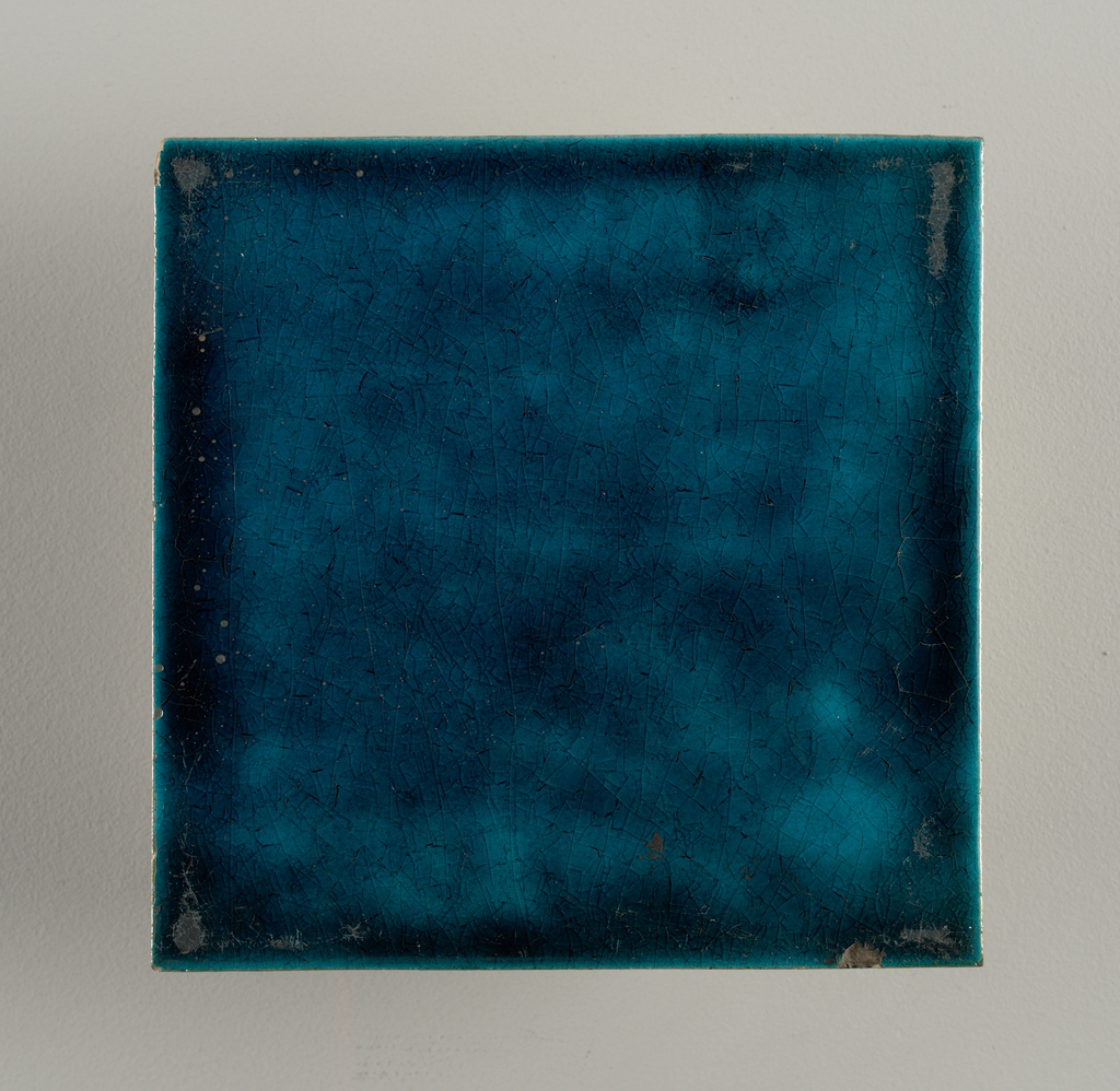 """Square tile of reddish buff clay with grog added. Brilliant greenish blue colored glaze, crazed. Stamped with double wing on back, surrounded by """"W. De Morgan 2 Co Sand's End Pottery"""""""