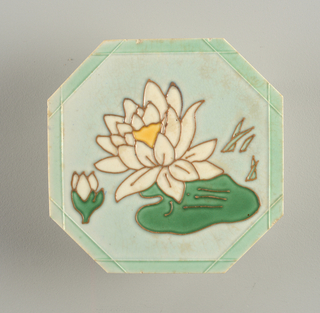 "Octagonal molded tile. Pale green border;center with paler green ground, molded in relief (""cloisonne"") with stylized white lotus blossom with yellow center, green leaf, bud and leaf, and water reeds."