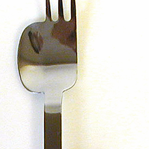 Stainless steel three tine fork with serrated, flanged edge extending from one side. Tubular, black plastic handle with flat top edge.
