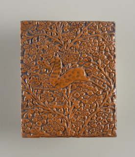 Vertical rectangle with molded decoration of leaping antelope against a dense floral and foliate pattern branching from a central stem.  Terracotta colored glaze heightened with blue.