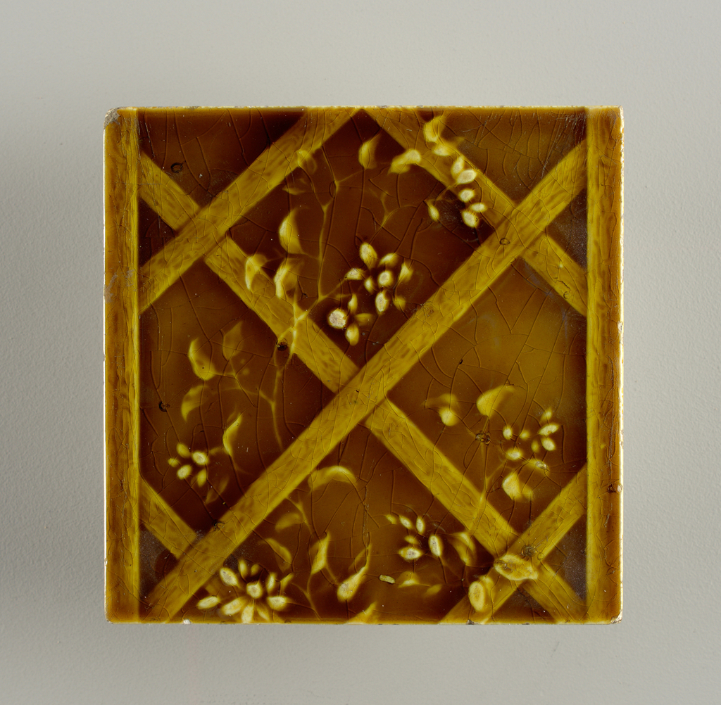 """Square molded tile of white clay; reverse relief parallel bands in plain frame, inscription: """"United States Encaustic Tile Co. Indianapolis, Ind. High Art Majolica No"""" Tile face decorated vertical lattice entwined with flowering vine. Deep honey-colored crackle glaze."""