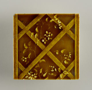 "Square molded tile of white clay; reverse relief parallel bands in plain frame, inscription: ""United States Encaustic Tile Co. Indianapolis, Ind. High Art Majolica No"" Tile face decorated vertical lattice entwined with flowering vine. Deep honey-colored crackle glaze."