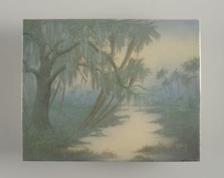 Rectangular plaque set into a plain oak frame. Cast, white stoneware plaque decorated with misty tropical scene with a tree covered with hanging moss in foreground and palm trees along the banks of a still river; more palm trees and foliage in background. Predominately in shades of greens, blues and blue-grays. Vellum glaze on front and partially on sides; cracklature. Back not glazed.