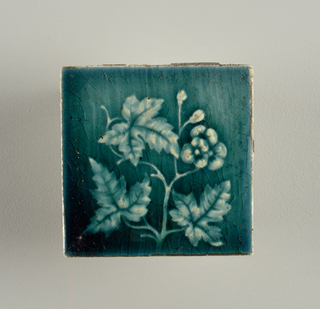 "Square molded tile made of white clay; reverse is pressed with a waffle patter, has a relief inscription: ""18 Provedential Tile Works"" Face of tile is decorated with a flowering branch, buds, flowers and marble-like leaves; teal green, crackle glaze."