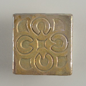 Molded buff composite stoneware and earthenware body with quatrafoil pattern, both recessed and in relief.  Covered with iridescent gray-brown glaze; felt backing.  Partially glazed on the edges.  Back is unglazed.