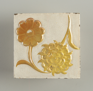 "Square tile od white clay with white crackled glaze. Two flowers with twisted stem in relief and painted with yellow lustre. Stamped on back: ""W. De Morgan"" in oval."