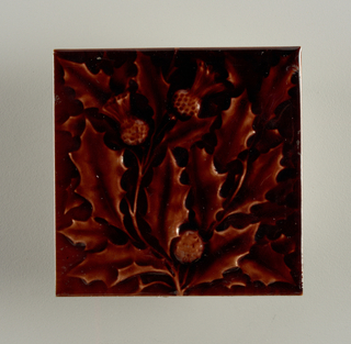 "A molded square tile of white clay. reverse has seven horizontal strips alternately impressed and raised; center impressed  strip has embossed: ""A.E. Tile Co. Limited"". Tile face has relief decoration of thistles and leaves painted glossy deep brown."