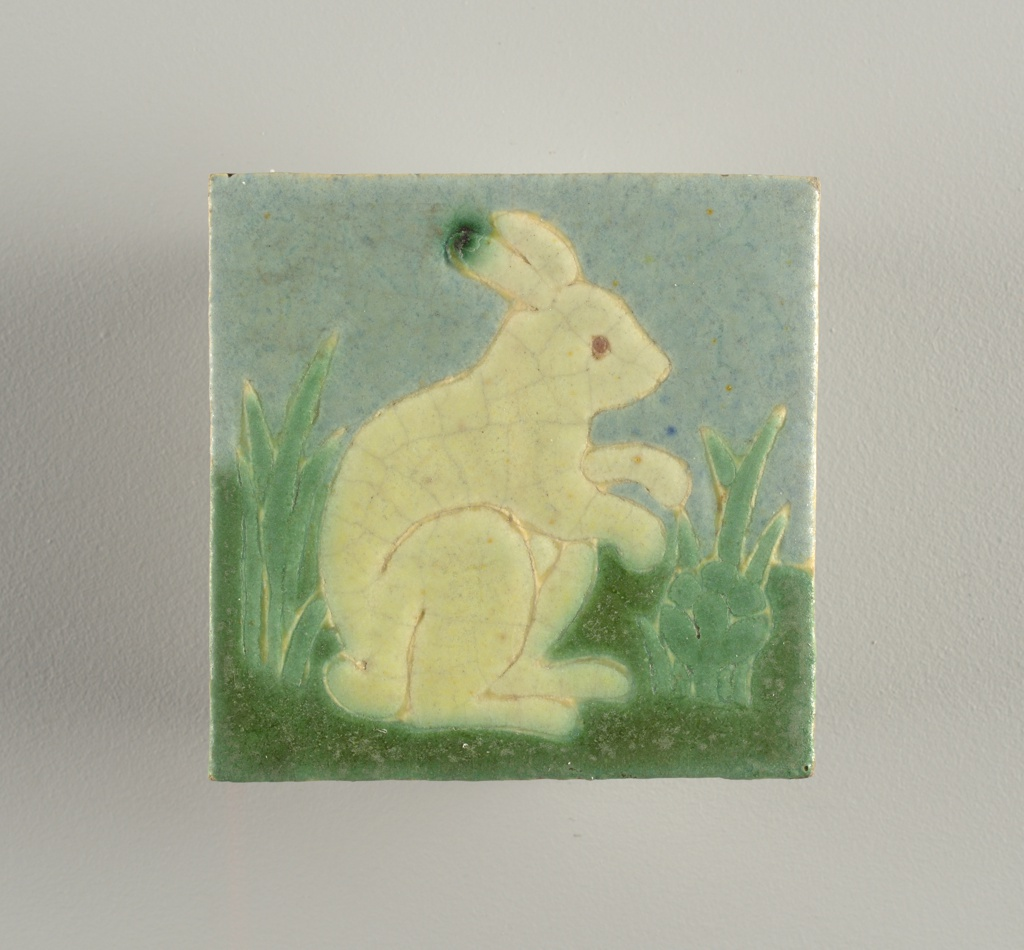 Gray-white earthenware body with press-molded design of rabbit crouching in grass. Light blue light and dark green, and pale yellow-green mat glzes defined by raised partitions.