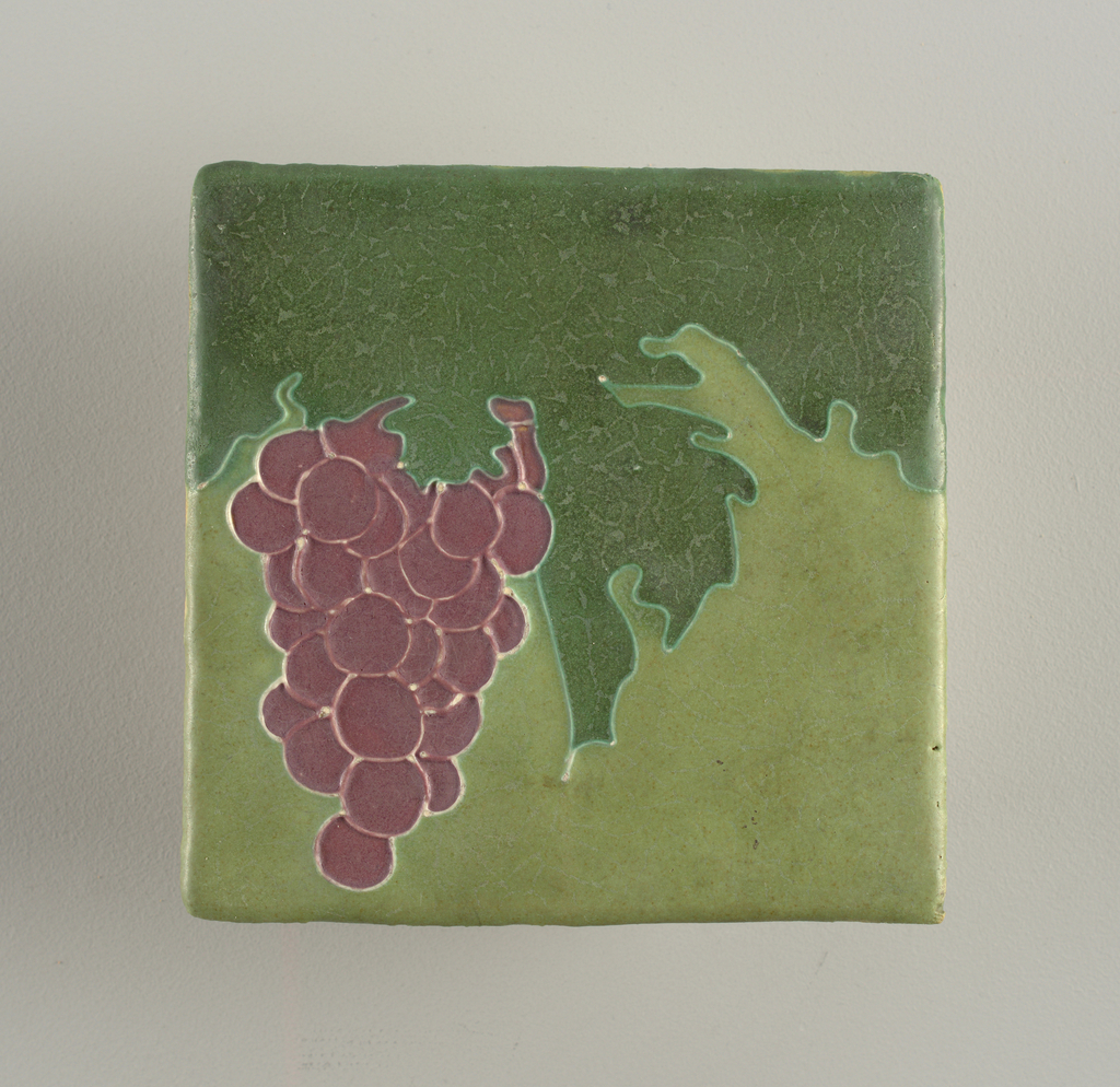 """Square molded tile of heavy yellow clay, reverse stamped """"Owens; face of tile decorated with grape bunch and leaves outlined with """"squeeze bag decoration"""", or slender thread like outlines. Glaze matte purple, pale and dark green."""