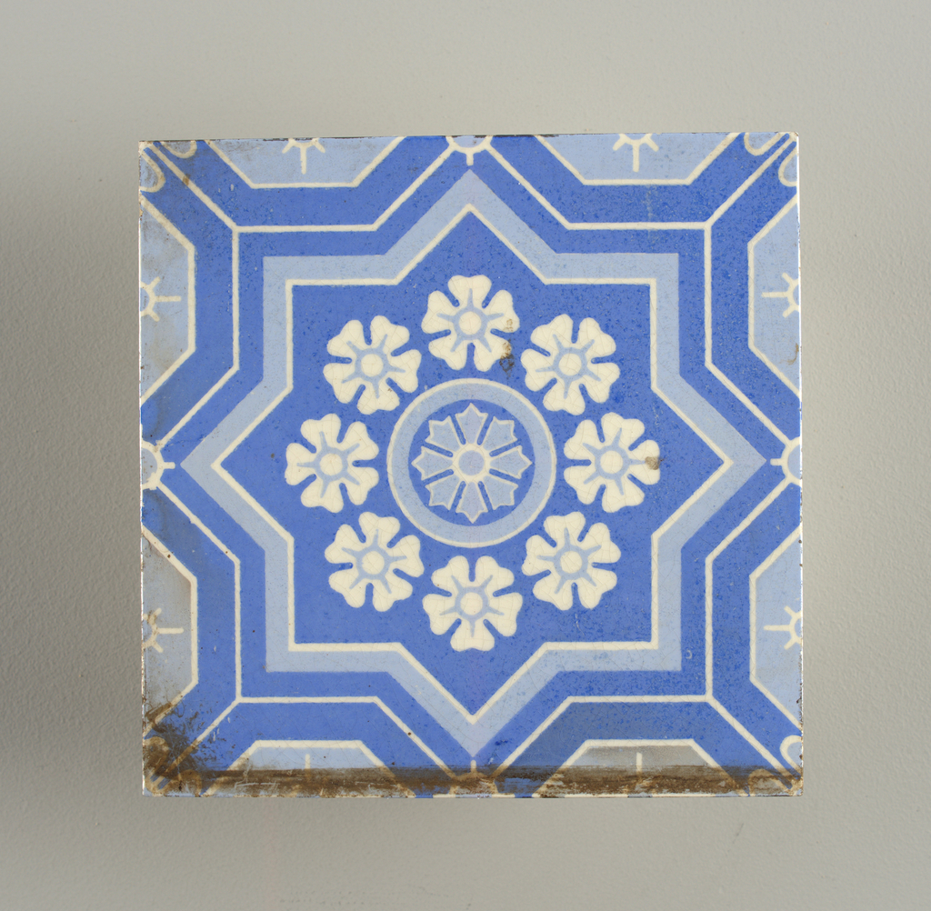 Square tile of white clay, overglaze with stenciled flower inside eight pointed star in two shades of blue.
