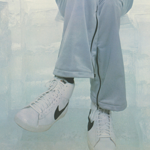 "Photograph of George ""The Iceman"" Gervin in a space filled with large ice cubes, holding a silver basketball in each hand, wearing a silver tracksuit with the word: 'ICE' embroidered on the chest. He wears white Nike sneakers. In lower margin: ICEMAN; lower left of photograph: NIKE logo."
