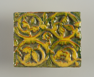 verticle rectangle. raised yellow and green Byzantine scrollwork with terra cotta outlines against green ground.