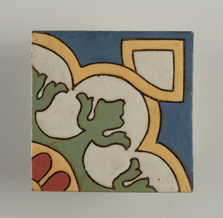 Square tile of rust earthenware stamped on reverse. Face of tile is decorated with an incised design depicting trefoil figure framed in an interlace band; matte glazes yellow, blue, red and green.