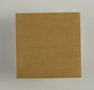 Square flat molded tile. Surface with metallic brass finish. Unglazed on reverse.
