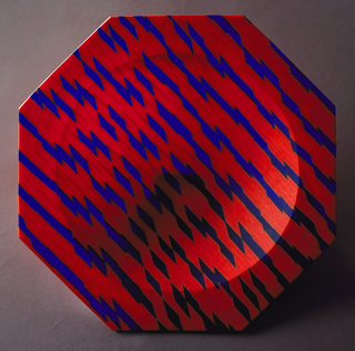 Octagonal bowl with broad flat rim.  Central circular concavity forming bowl, with rounded underside.  Bowl is fabricated of twisted canes of semi-opaque red-orange glass with deep transparent blue.  Strips are heat-laminated together to create pattern of blue parallelograms on a red ground, the pattern arranged perpendicular to the direction of lamination.  Entire bowl wheel-cut; wheel marks visible front and back.