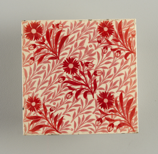 Square tile of white clay (commercial production). White glaze painted with diagonally placed small stems and leaves in pale rose and crosswise overlaid with conventionalized pinks in cherry red. Back ribbed.