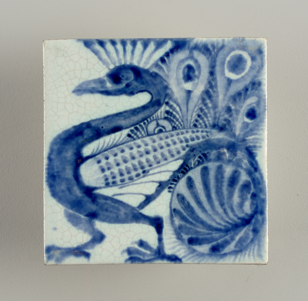 Square tile of reddish clay with grogg added.  Bluish-white crackled glaze with peacock painted in blue.
