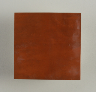 Square flat molded tile. Surface with metallic copper finish. Unglazed on reverse.