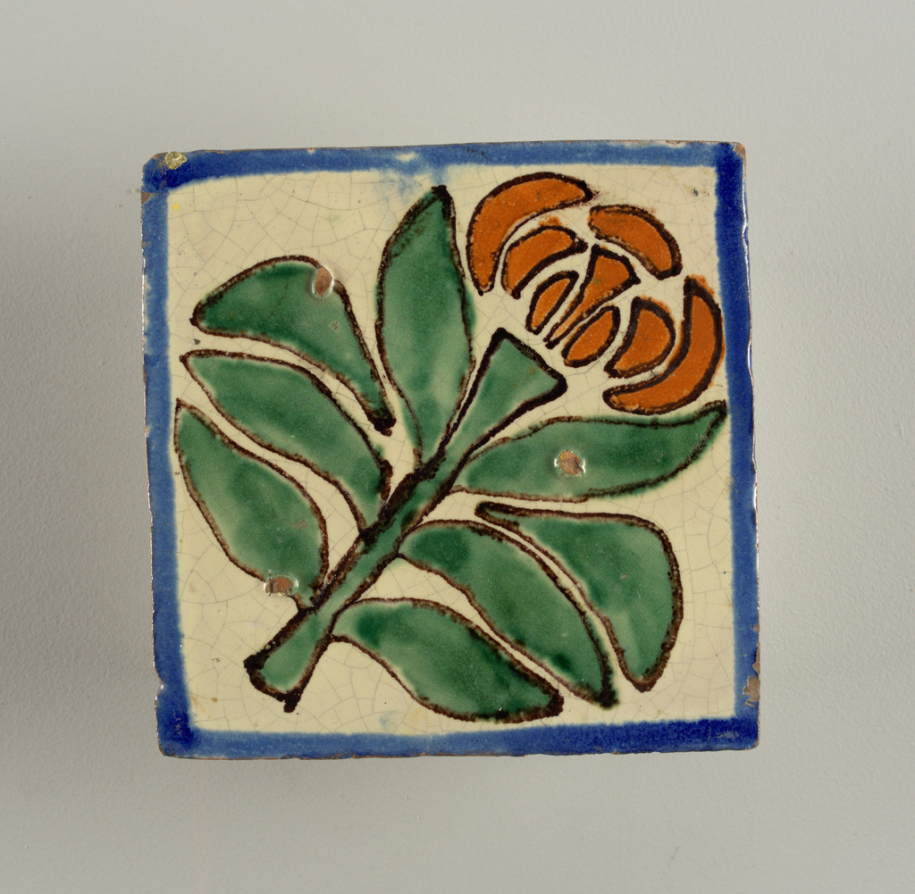 Square tile, terra cotta earthenware; reverse uneven surface, no marks. Tile face decorated with stylized tulip flower, parts of plant separated. Painted with black borders, placed diagonally on surface; red petals, green leaves, narrow plain blue border on cream crackle glaze.
